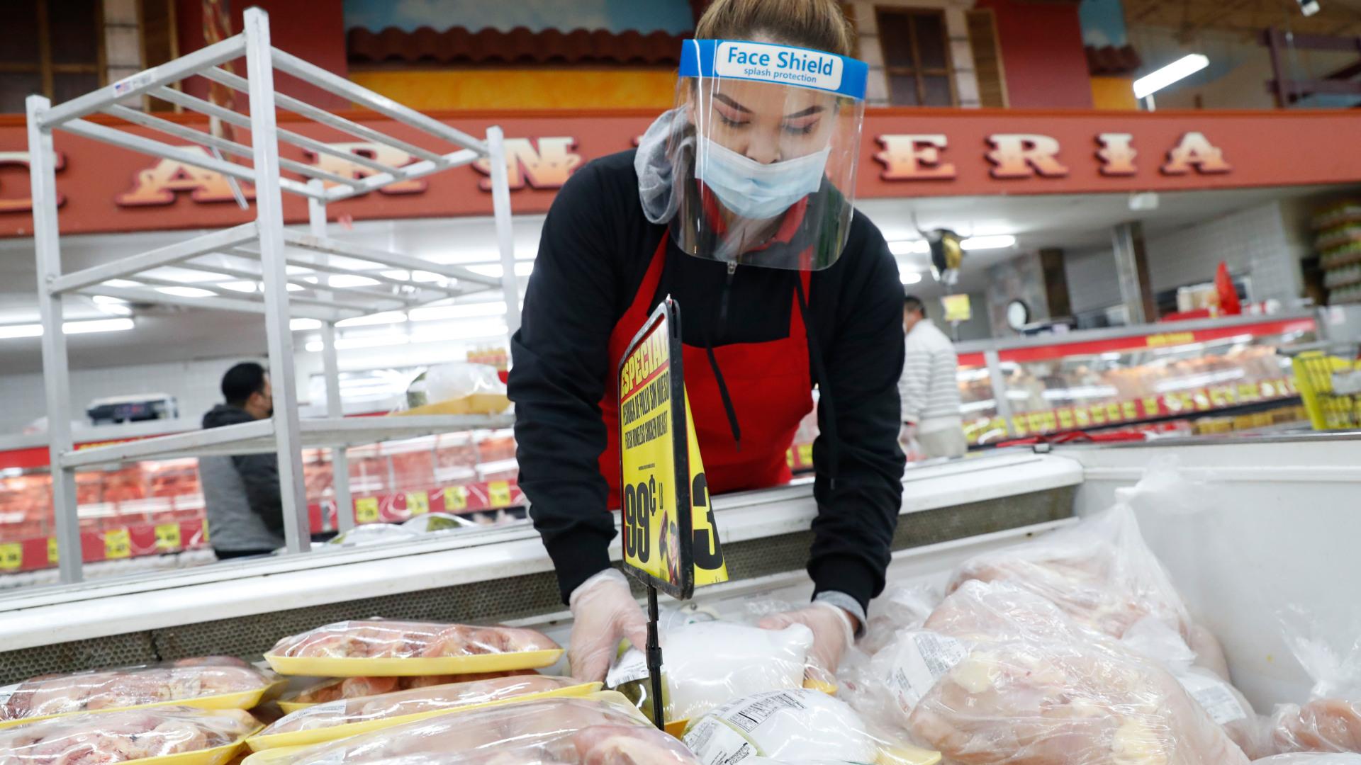 A worker stocks meat in the frozen food aisle.
