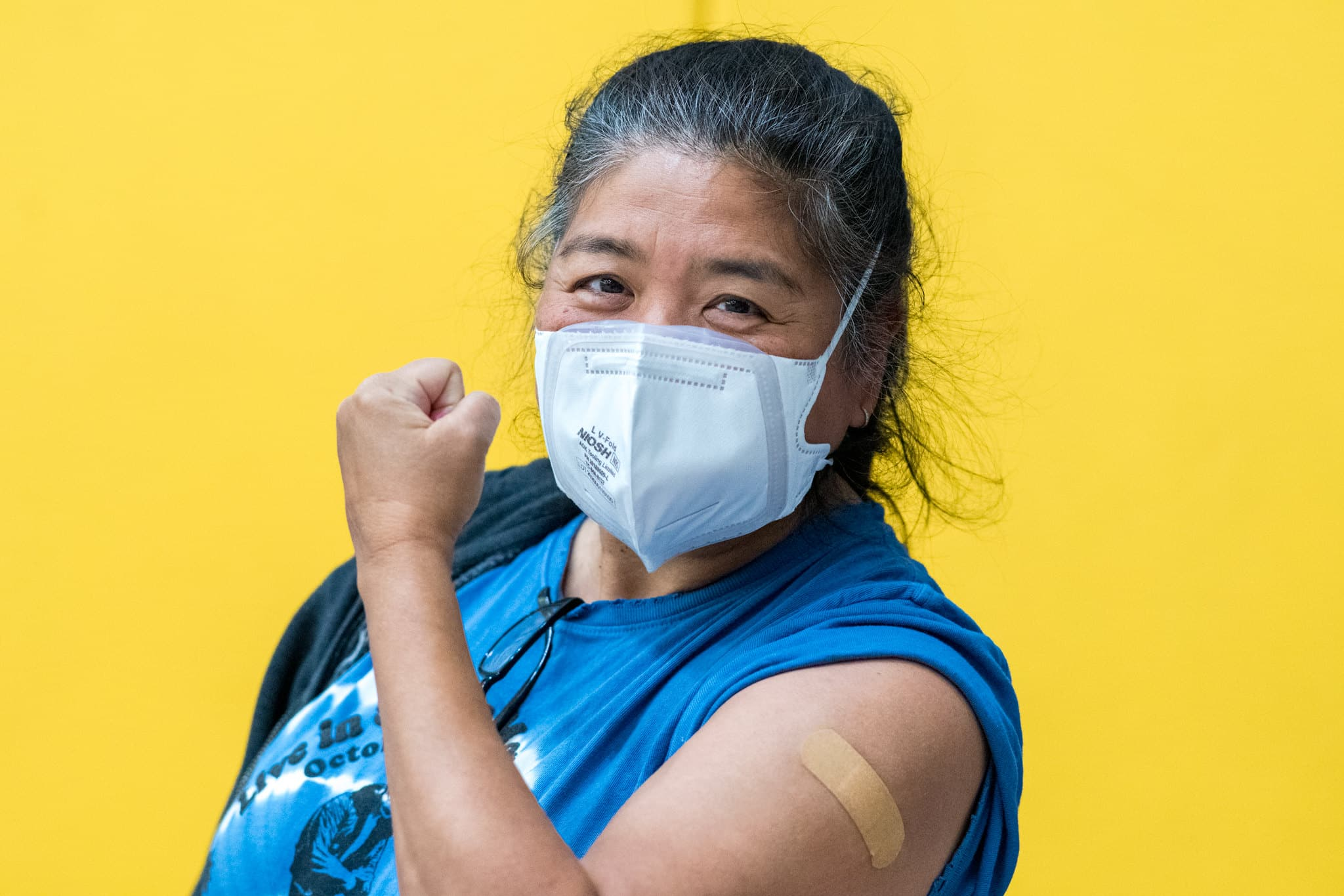 A woman shows off her arm where she received a COVID vaccine.