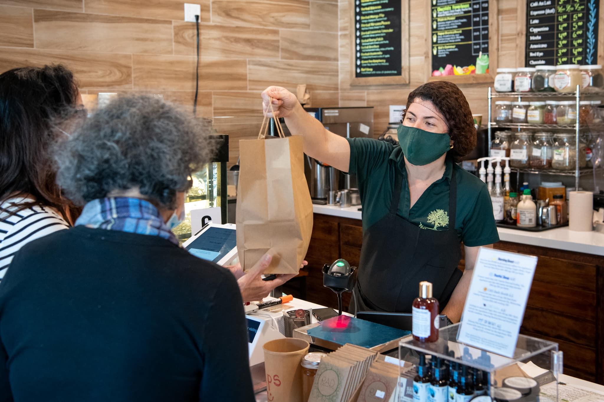 A server hands a customer a bag of food